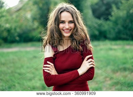 Portrait Of Confident Beautiful Smiling Woman With Crossed Outdoors On Green Summer Nature Backgroun