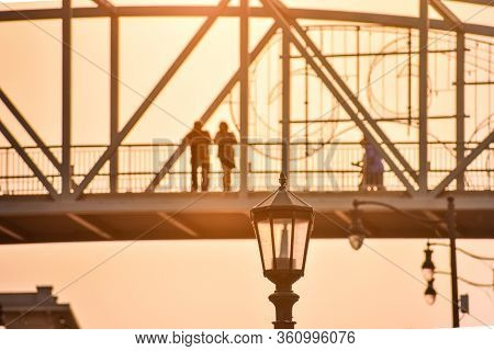 Unrecognizable Couple Contemplating The Views On A Bridge Against The Sunset. Streetlight In The For