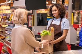 Pretty young cashier giving mature female paperbag with bread and fresh groceries while both standing by cash register in supermarket