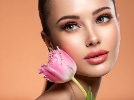 Beautiful white girl with flower. Stunning brunette girl with  pink tulip. Closeup face of young woman with a healthy clean skin. Pretty woman with bright makeup