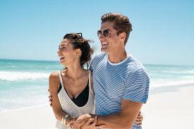 Young couple embracing while walking on beach. Young man and beautiful woman in a relationship enjoing summer vacation in a tropical beach. Happy carefree couple holding hands at seaside feeling free.