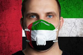 Young Man With Sore Eyes In A Medical Mask Painted In The Colors Of The National Flag Of United Arab