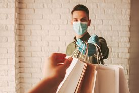 Girl Receiving Paper Parcels From Online Delivery Service. Delivery Man Courier In Medical Face Mask