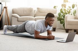 Training At Home. Sporty Man Doing Yoga Plank While Watching Online Tutorial On Laptop, Exercising I