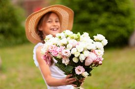 A Smiling Girl Holds A Beautiful Bouquet Of Pink And White Peonies In Her Hands. A Child In A Straw