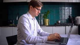 A Man Works In The Kitchen At A Laptop At Home. Concept For Remote Work At Home During The Coronavir