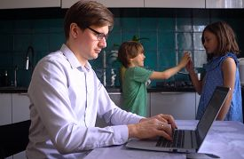 A Man Works In The Kitchen At A Laptop With His Children At Home. Father With Son And Daughter. Remo