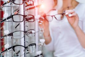 Row Of Glasses At An Opticians. Eyeglasses Shop. Stand With Glasses In The Store Of Optics. Woman Ch