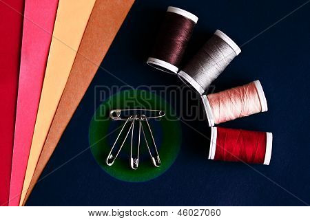 Sewing kit with safety pins on rainbow background