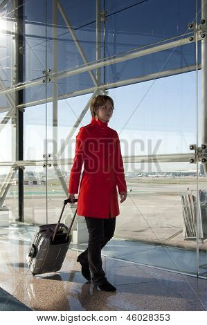 Businesswoman At Airport Traveling With Trolley In Red Coat