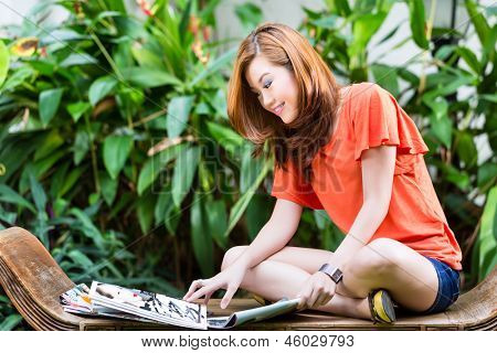 Young Chinese girl sitting on a bench in a tropical environment and reading a fashion magazine, she is fashion-conscious