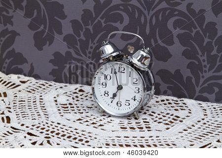 Antique Alarm Clock On Table Cloth