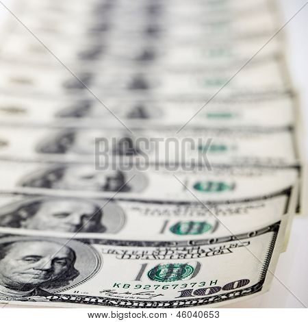 Lots of 100 US dollar bills in a line. Selective focus
