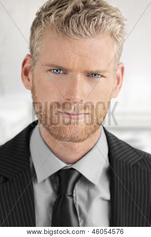 Fashionable young handsome business man with nice blue eyes in suit