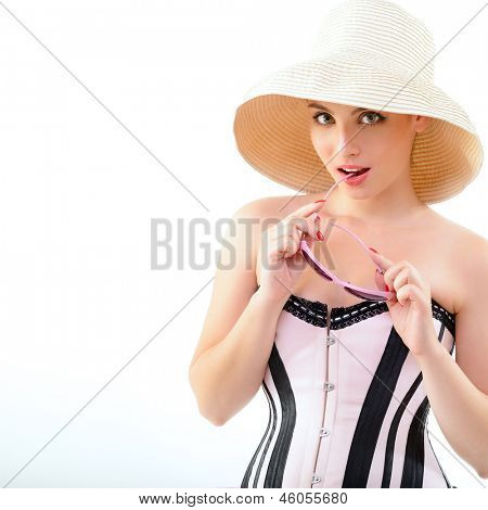 Summer pinup girl, portrait of young happy sexy woman in pin-up style in panama hat with sun glasses, over white