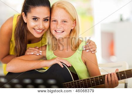 attractive music tutor and preteen girl with a guitar