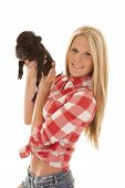 a woman in her plaid top and jean shorts holding on to her pet pig. poster