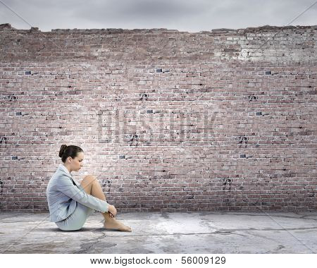 Image of young upset businesswoman sitting alone