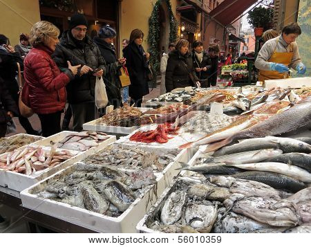 Crowd Of People In Front Of A Stand Of Fresh Fish At The Market Outdoor For Shopping