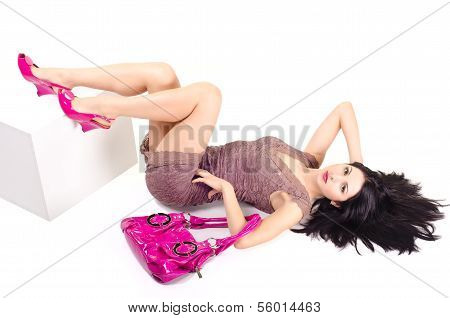 Woman lying on the floor and holds on hand bag