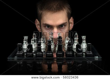 Chess Master staring at you with intense eyes behind glass chess pieces on a glass chessboard with a reflection isolated on a black background poster