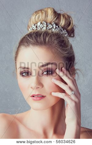 Portrait of a beautiful blond bride with a diamante headpiece. Hair in romantic top knot bun hairstyle.