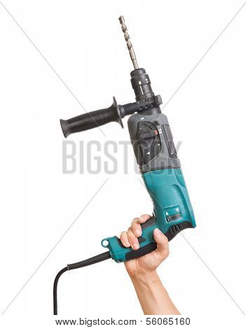 Hand holding electric drill with stone bit. Tool has some signs of usage.