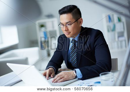 Smiling businessman in suit typing on laptop in office