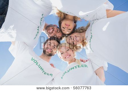 Low angle portrait of happy volunteers forming a huddle against blue sky