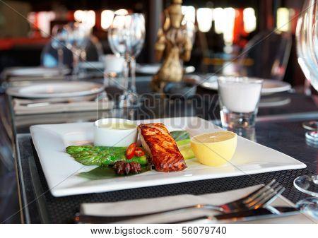 Asian style salmon steak on restaurant table poster