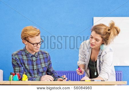 Two designers at work, co-designing a product, with markers in various colors in a colorful office with a white board and a blue wall