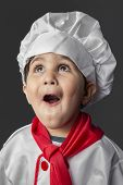 Funny, little boy preparing healthy food on kitchen over grey background, cook hat poster