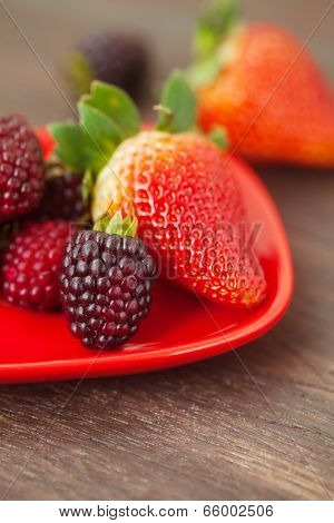 Red Juicy Strawberry And Blackberry In Red Plate On A Wooden Surface