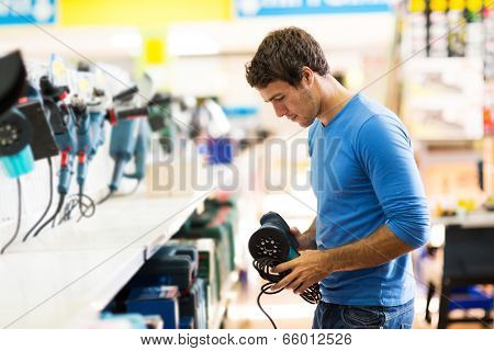 handsome young man shopping for sander in hardware store