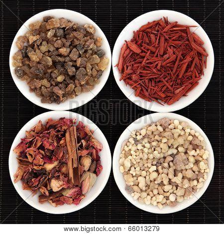 Frankincense, myrrh, sandalwood and fragrant rose pot pourri over bamboo background.