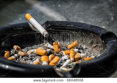 Burning Cigarette On Dirty Ashtray
