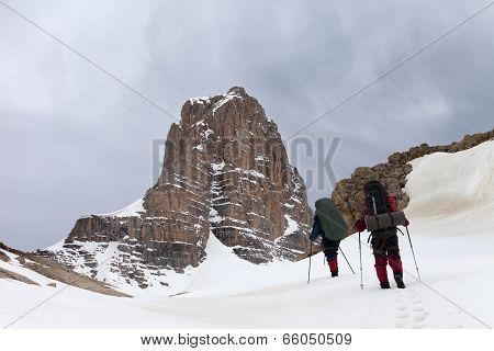 Two hikers in snowy mountains before storm. Turkey Central Taurus Mountains Aladaglar (Anti Taurus) plateau Edigel (Yedi Goller). poster