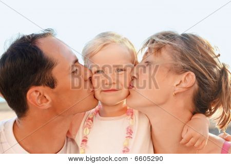Happy Family With Little Near To Sea, Parents Kiss Daughter