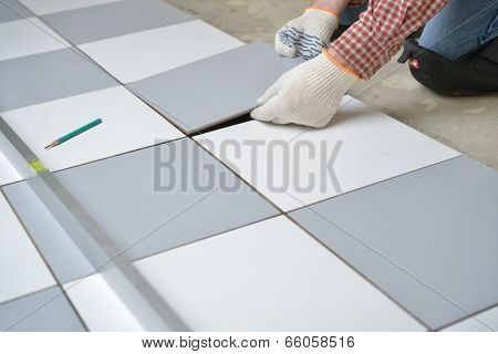 Tiler install ceramic tiles on a floor poster