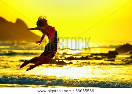 young woman jumping on the beach in summer sunset light