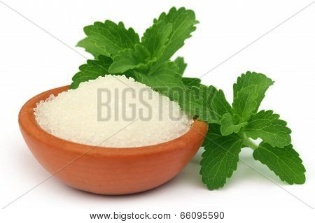 Stevia with sugar on a brown bowl over white background poster