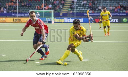 THE HAGUE, NETHERLANDS - JUNE 2 2014: Englishman Catlin reaches for the ball to stop a rush by Indian player Manpreet during the Hockey World Cup in the match between England and India. GBR beats IND 2-1