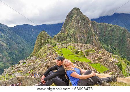 Inter ethnic couple of tourists on Sun Gate, (Machu Picchu, Peru)