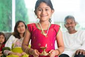 Indian family celebrate diwali or deepavali at home, little girl with traditional clothing sari, hands holding oil lamp indoor. poster