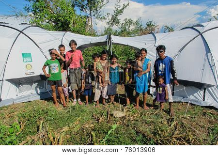 Filipino Families In Front Of Their Disaster Relief Tent after typhoon Haiyan struck November 2013