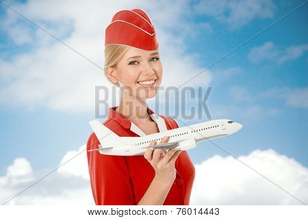 Charming Stewardess Holding Airplane In Hand. Sky With Clouds Background.
