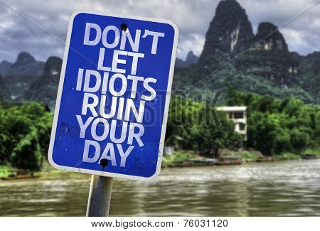 Don't Let Idiots Ruin Your Day sign with a forest background