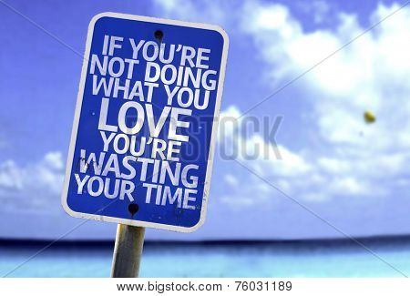 If You're Not Doing What you Love You're Wasting your Time sign with a beach on background