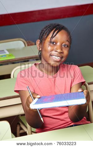 African girl holding school book in elementary school class
