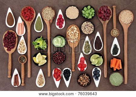 Large diet and weight loss superfood selection in bowls and spoons over lokta paper background.